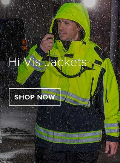 Man walking in the rain at night time wearing a Hi-Vis Jacket using a handheld radio.